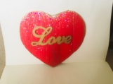 Wooden red heart with gold edges and the word love in the center