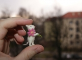 Super cute and tiny white mouse with pink flower