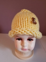 Hand knit toddler girl's ponytail hat in soft yellow.