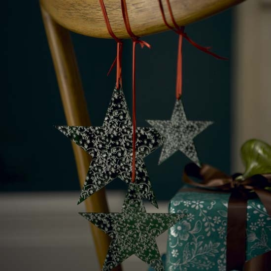 Tie tree ornaments, like stars, to the back of your chairs