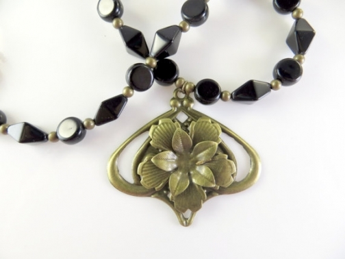 Black and gold beaded necklace with flower.