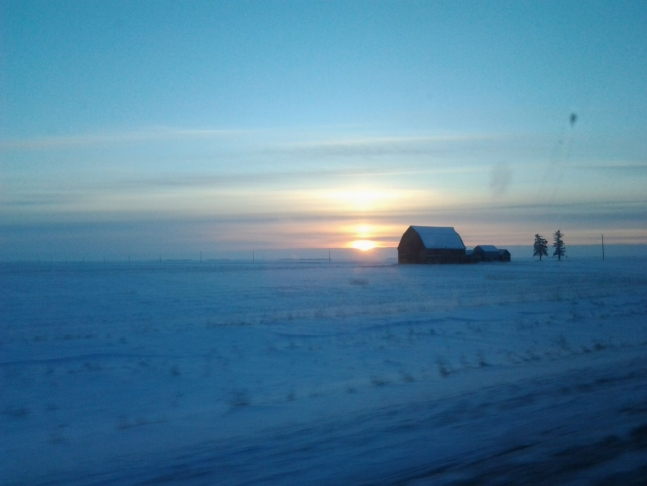the sun rises in a cold winter sky next to a barn and outbuildings huddled on the open prairie